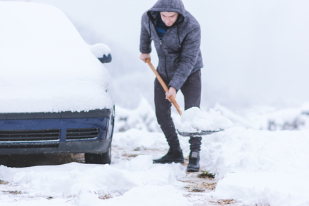 Man dressed in jacket cleaning snow around his car. Prepearing for travelling. Stock Photo
