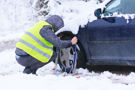 Man prepearing car for travelling at winter day. Snow chains on the wheels of car.