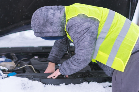 Man dressed in neon green safety vest trying to repair his car at cold winter day. Stock Photo
