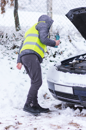 Man dressed in neon green vest pouring motor oil to car engine at cold winter day.