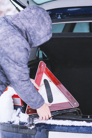 Man taking safety car triangle from luggage of his damaged car.