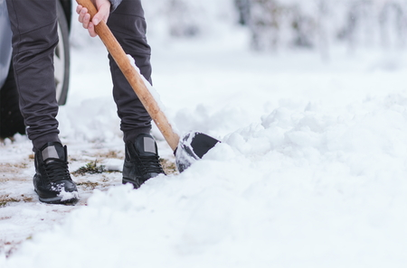 Young male person cleaning snow at backyard. Cold snowy winter day. Close up view on legs and shovel. Stock Photo