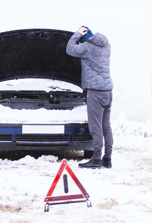 Seriously worried male person standing in front of damaged vehicle at cold winter day.
