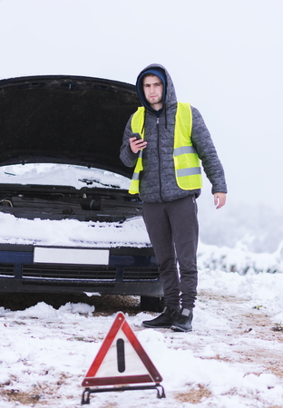 Man dressed in neon green safety vest calling winter car services to help. Stock Photo