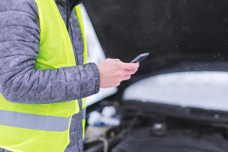 Close up view. Man holding mobile phone and calling winter car services to help.