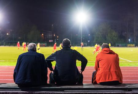 People watching football match at night Foto de archivo