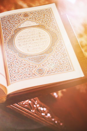 Light beam of hope over quran - Holy book of Muslims. Quran in mosque open for reading and prayer Stock Photo