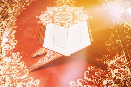 Light beam of hope over Koran - holy book of Muslims. Quran in mosque open for reading and prayer