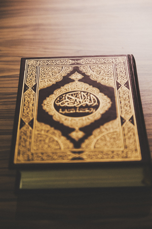 Quran - Holy book of Muslims. Quran book on wooden brown background.
