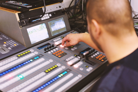 TV editor working with audio video mixer in a television broadcast studio desk station