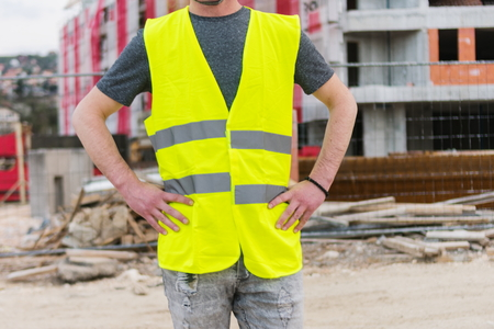 Young engineer working on construction site building architecture project. Construction Worker dressed in hard yellow vest Stockfoto