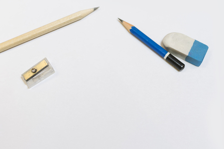 Top view of hand writing with wooden pencil on a white paper using writing accessories. Business, education concept.