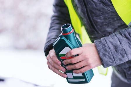 Close up view of hands with bottle pouring motor oil to car engine at cold winter day. Stockfoto