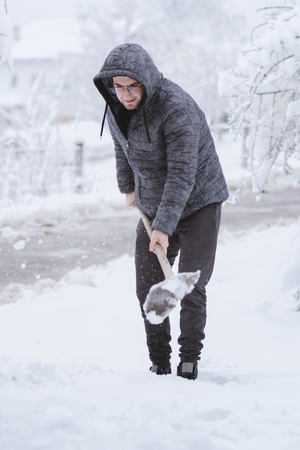Young male person cleaning snow at backyard. Cold snowy winter day.