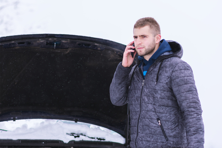 Man standing in front of damaged vehicle and calling car services to help. Man solving problems with car.
