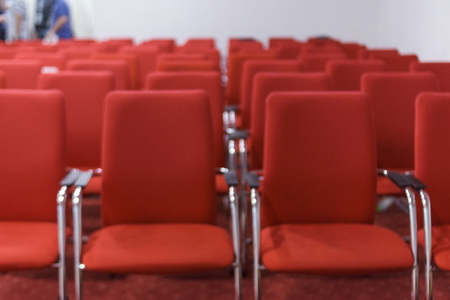 Rows o modern red chairs arranged in the main conference room.
