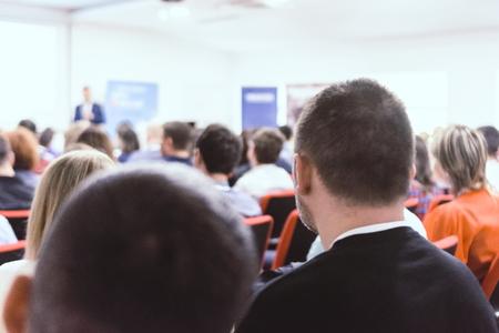 Młodzi i odnoszący sukcesy ludzie na seminarium biznesowym i dotyczącym danych, słuchając prezentacji. Koncepcja biznesu i sukcesu.