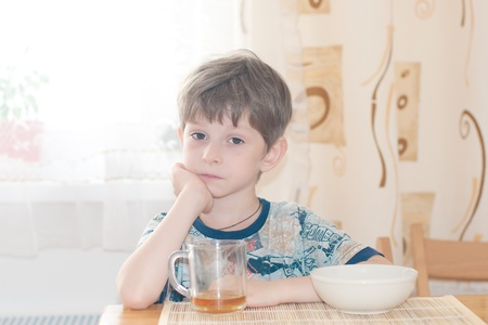 munching: The nice boy with sad eyes during a breakfast  Stock Photo