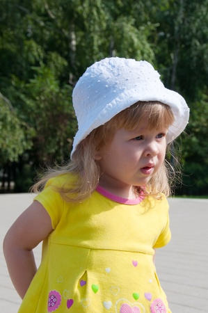 curly headed: The beautiful little girl on walk in park  Stock Photo