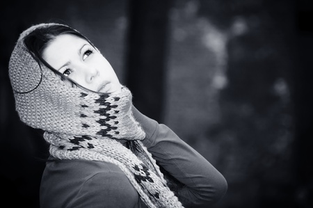 The young woman in a scarf and a cap to a cap with ear-flaps photo