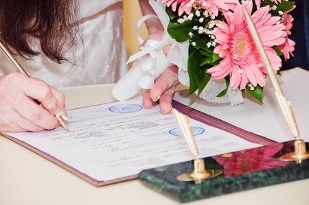Newly-married couple signs documents 版權商用圖片