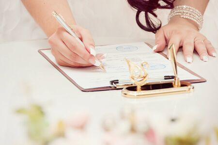 Newly-married couple signs documents Stock Photo