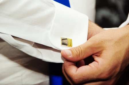 A groom putting on  cuff-links as he gets dressed in formal wear .Grooms suit photo