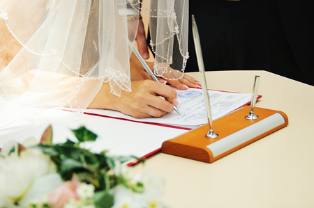 Bride signing marriage license or wedding contract Stock Photo