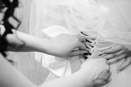 zip tie: Helping the bride to put her wedding dress on Stock Photo
