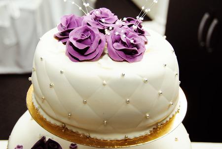 White wedding cake with purple flower detail photo