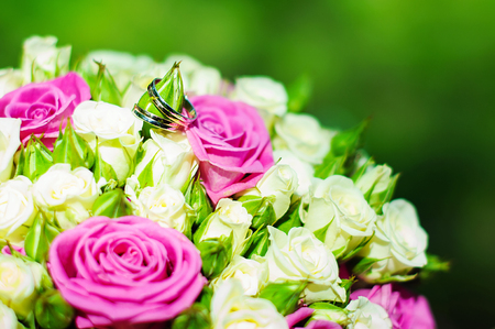 Rings of a newly-married couple on a bouquet of the bride photo