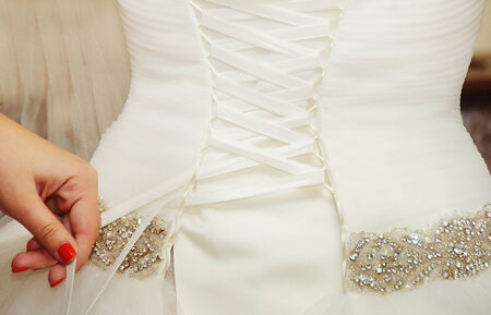 zip tie: Helping the bride to put a  wedding dress on Stock Photo