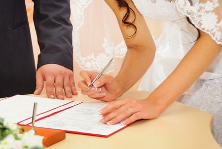 firmando: Novia firma la licencia de matrimonio o contrato de la boda Foto de archivo