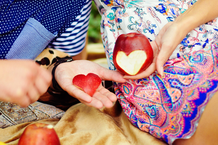 Womans hand with apple, which cut a heart photo