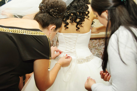 Helping the bride to put her wedding dress on Stock Photo