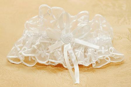 White wedding garter for the beautiful bride photo