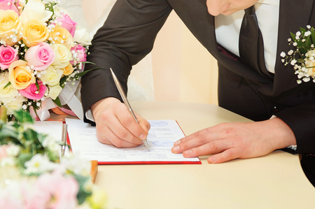 Groom signs the marriage contract or the document Stock Photo