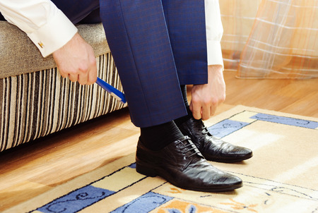 Man puting on his shoes. Stock Photo