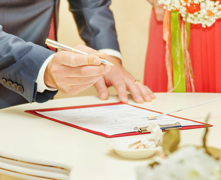 marriage certificate: Bride and Groom Signing Marriage Certificate or contract Stock Photo