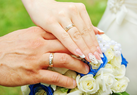 married couples: Bride and groom hands and rings on wedding bouquet