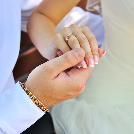 Bride and groom holding hands in wedding day