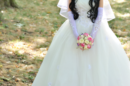 flowergirl: Bride holding colorful bouquet with her hands on wedding day