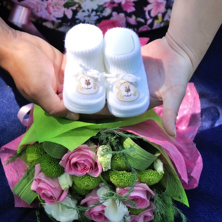 Knitted baby shoes for boy in mother hands Stock Photo