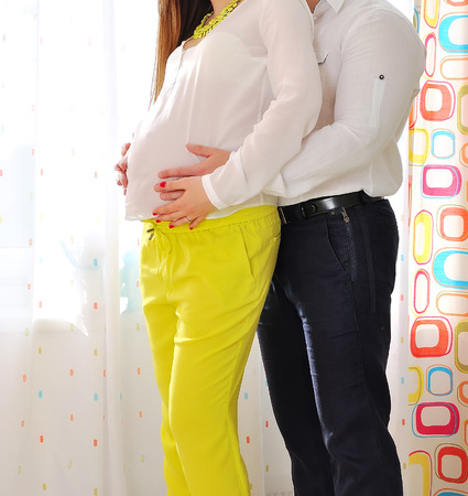 Image of pregnant woman touching her belly with hands Stock Photo