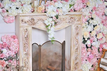 Elegant white fireplace full of flowers. Elegant room Banque d'images