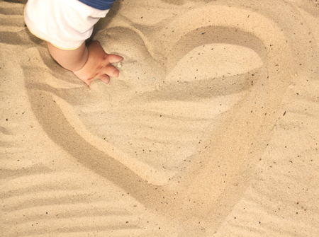 sand drawing: Child playing with sand, drawing a heart in the sand