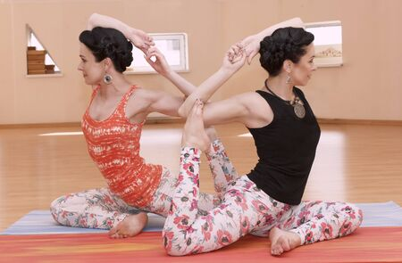 indoors: Two young women do yoga indoors