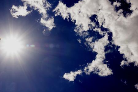 sun and cumulus white clouds against a beautiful blue sky, bizar Stock Photo