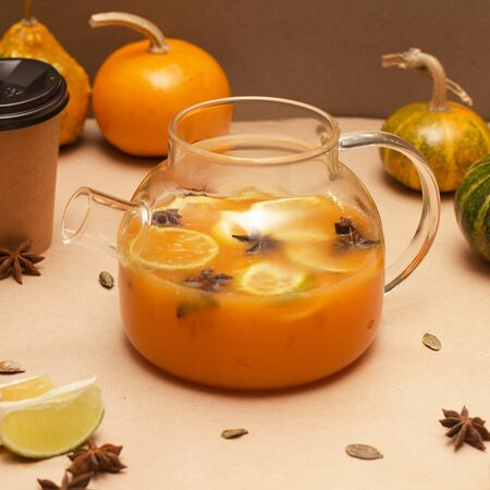 Pumpkin tea in a glass teapot with a lemon on background.-Image