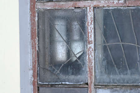 desolation: Old frosted window of an abandoned building in winter.